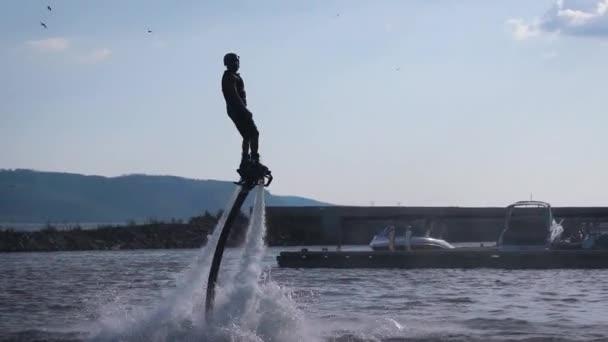 Sportive men doing flip with jetpack over water