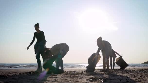 Děvčata dobrovolníci čistí pobřeží před odpadky. Ženy zásobují odpadky na břeh v černých taškách. Ekologická dobrovolná akce.