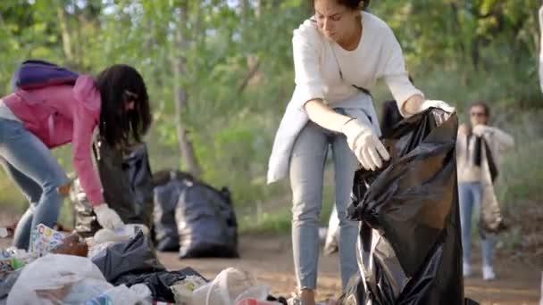 Ženy dobrovolníci likvidují velkou skládku. Nelegální skládka v lese kazí přírodu a ekologii. Dobrovolníci dělají světu čistší místo.