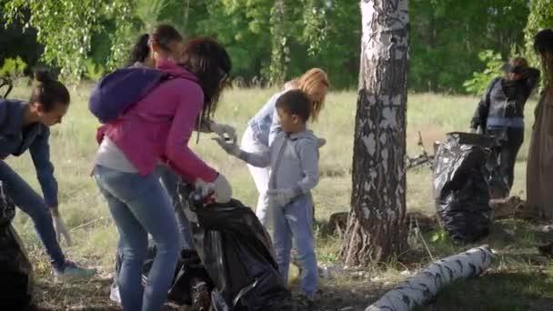 Eine Gruppe von Frauen und Kindern sammelt Müll im Wald. Freiwillige sammeln Plastik und andere Abfälle in schwarzen Plastiktüten. Die Menschen sind für die Umwelt verantwortlich.