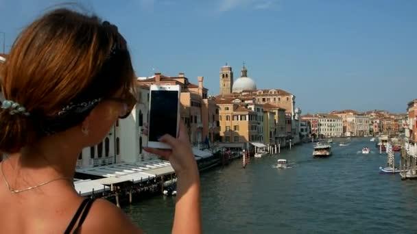 Touristin mit Smartphone in Venedig, Italien. Das Mädchen macht ein Foto von Venedig für soziale Netzwerke