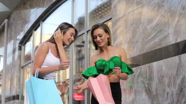 Dvě šťastné mladé ženy, které se navzájem ukazují v nákupních taškách, diskutují o nich a smějí se