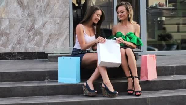 Két boldog fiatal nő, akik bevásárlószatyrokban vásárolnak, beszélgetnek róluk és nevetnek, miközben a pláza közelében ülnek.