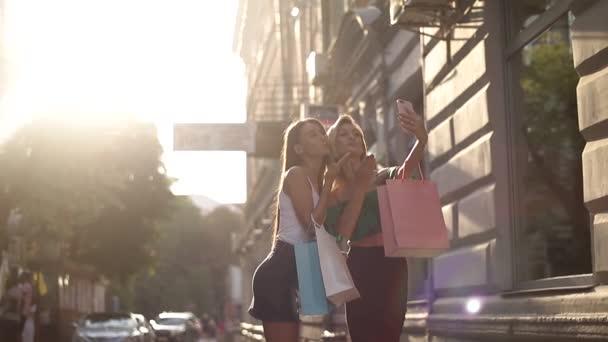 Zwei schöne Mädchen machen Selfies auf der Straße, zwei Mädchen kaufen ein
