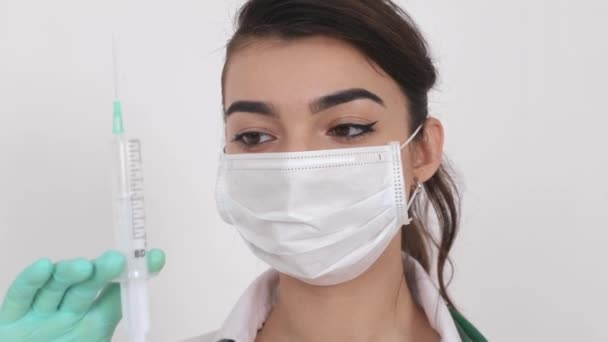 A girl doctor in a medical mask that holds a syringe with vaccination against coronavirus (COVID-19).