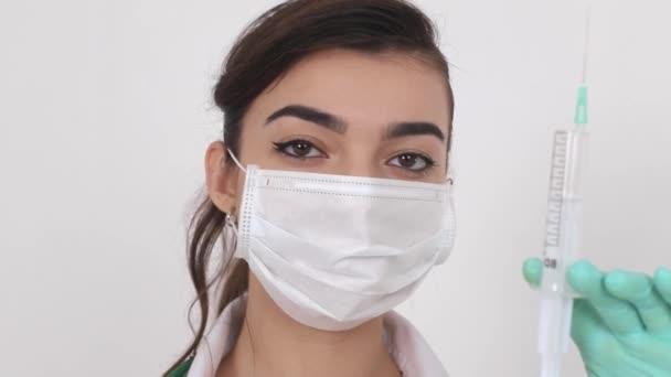 Ein Virologe in einer medizinischen Maske hält eine Spritze mit einem Impfstoff gegen Coronavirus (COVID-19) in der Hand.