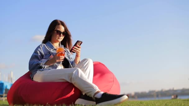 Das Mädchen trinkt einen Orangencocktail