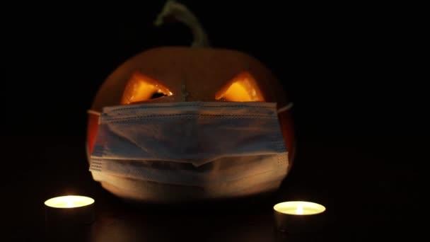 Halloween faragott tök izzó védő orvosi arc maszk, koronavírus és karantén koncepció, covid-19 halloween jelmez. A szemek megváltoztatják a fényességet. Fehér füst.