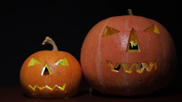két gyönyörű tök narancs elszigetelt sötét háttérrel, halloween ünnep koncepció, közelkép, másolás tér