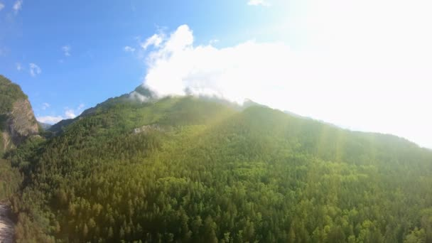 Panorama of amazing mountains with green forest, blue sky and bright sunlight