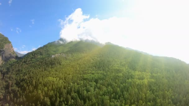 Panorama of beautiful mountains with green forest, blue sky and bright sunlight