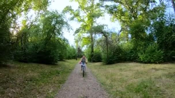 Na kole v parku. Dívka na koni na kole na lesní cestě