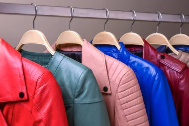 New collection of different color spring leather jackets for women. Colorful background of modern spring, autumn outerwear. Close up. Seasonal clothing in store on sale.