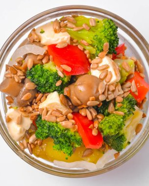 Healthy food - mix vegetable salad served in a bowl over white background. Healthy eating, delicious snack or dinner. Plate close up, fresh organic greenery.