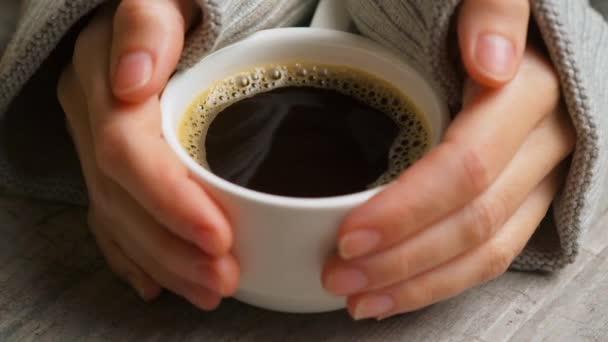 Boční pohled na ruce s šálkem černé kávy na světle dřevěné pozadí stolu. Bílý šálek černé kávy. Jemné ženské ruce si dávají šálek kávy. Selektivní zaměření, zavřít.