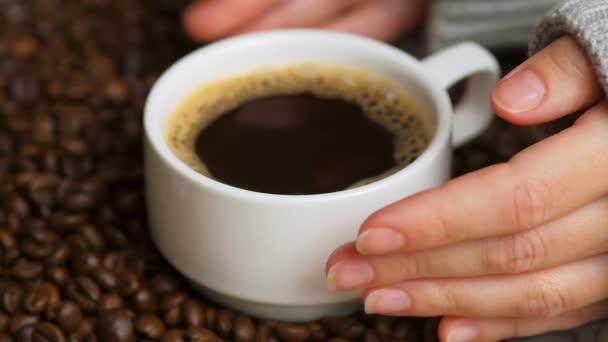 Boční pohled na ruce s šálkem černé kávy na kávových zrn pozadí. Bílý šálek černé kávy. Jemné ženské ruce si dávají šálek kávy. Selektivní zaměření, zavřít.