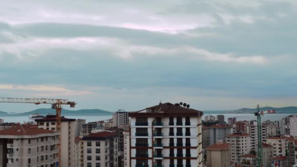 Timelapse of high angle view city scenery with running gray clouds in Kadikoy, Istanbul, Turkey. Construction with cranes concept.