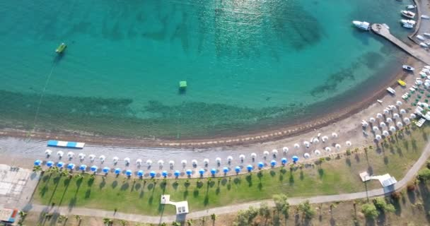 Aerial view of transparent turquoise sea, beautiful sandy beach with white chaise-lounges, umbrellas, palm trees at sunrise. No people, Cape Tisan on the Mediterranean sea coast.