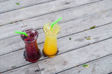 Juice mix berry, mango and passion fruit drink in tall glass with straw green color on wooden terrace