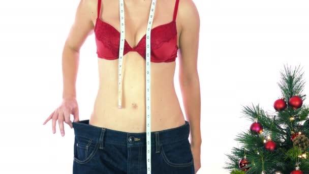 Hubená žena v červené podprsence s měřicí páskou ukazující velké kalhoty a jablko. Koncepce diety, hubnutí a tělesné kontroly, přibývání tuku a štíhlé dolů během vánočních svátků, dobré úmysly