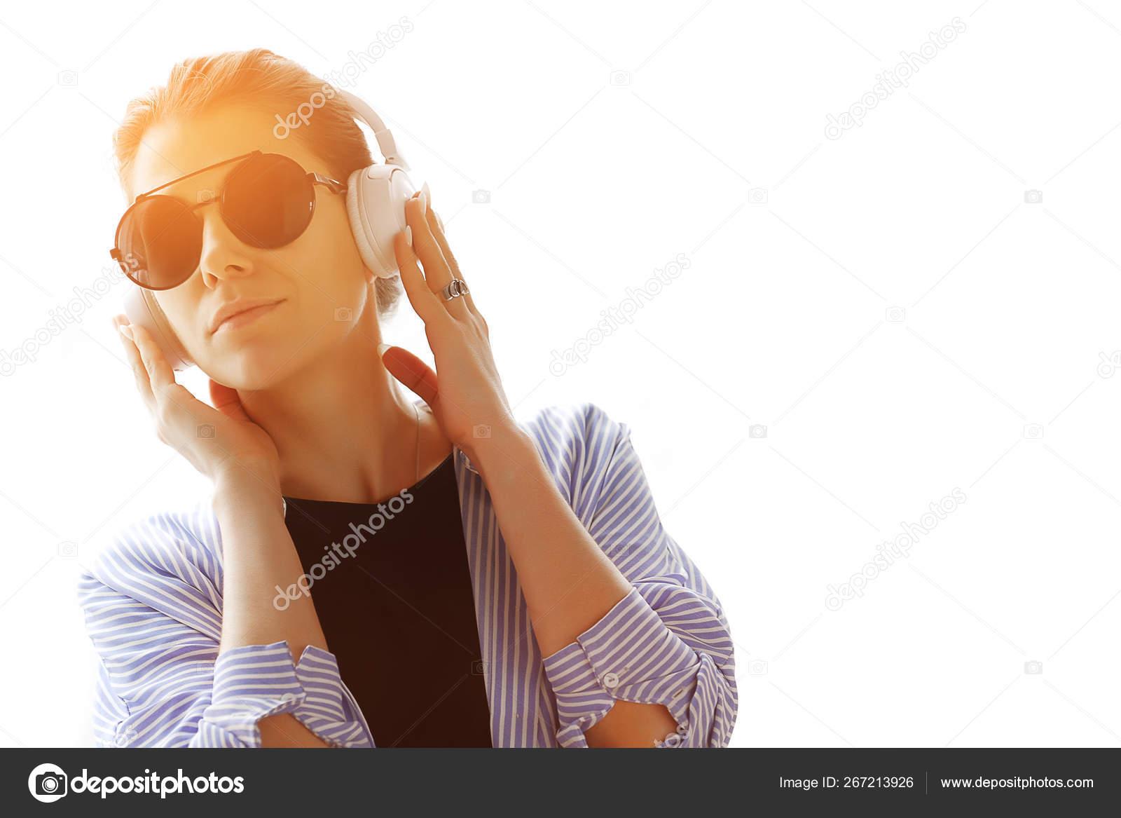 Beautiful brunette girl in stylish glasses and headphones listening