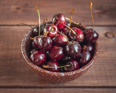 Ripe large sweet cherries in a deep ceramic brown bowl on an wooden tray