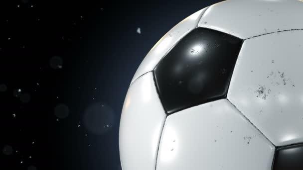 schöner Fußballball, der in Zeitlupe in Großaufnahme auf schwarz rotiert, wobei Staubpartikel fliegen. geloopter Fußball 3D-Animation des Drehens von Ball. 4k uhd 3840x2160.