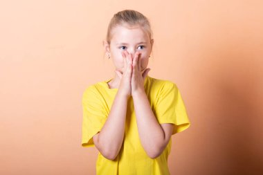 Beautiful little girl is embarrassed on a light orange background.