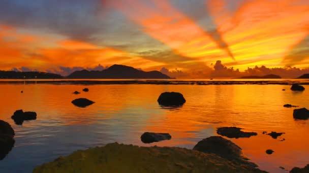 scenery reflection of beautiful sunrise in Rawai sea. amazing morning light shines through the colorful sky.