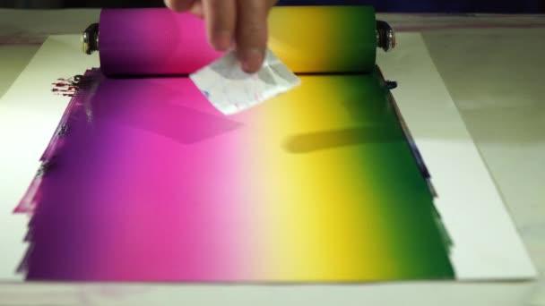 Míchání barev pomocí válečku k otočení barev tak, že každá barva je smíchána dohromady a pak se válí na šablonu vytvořit grafické umění.