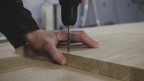 A man drills a hole in a wooden billet