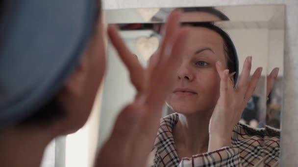 Portrét krásné zdravé ženy, která na tváři zvlhčující krém.