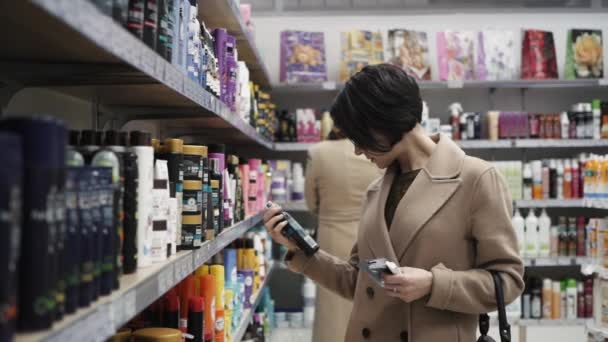 Beautiful woman looking at cosmetics in supermarket.