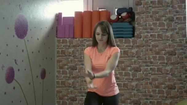 Lány fitness oktató mutat egy sor gyakorlatok az edzőteremben