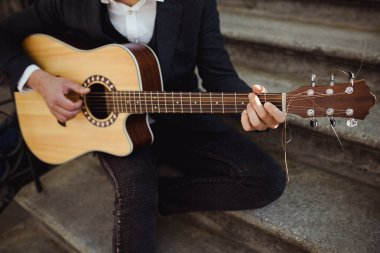 Man in casual outfit playing guitar , close up. Young hipster siting on the stairs
