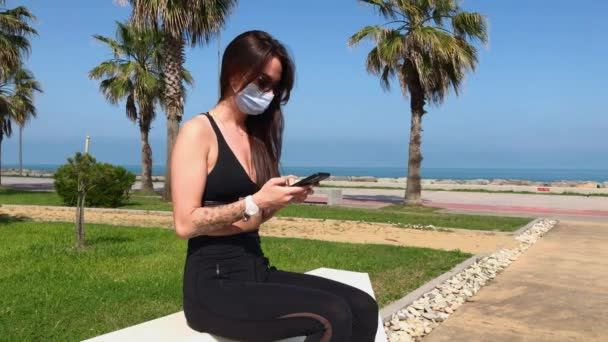 Girl Wearing Face Medical Mask Uses Smartphone in the Park. Prevention of infection Coronavirus or Covid 19 in the Air. Air Pollution Protection.