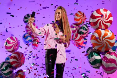 Girl in headphones with a smartphone, sings a song, on a purple background of candy, colored balloons
