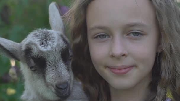 Mosolygó szerető lány játszó kisgyerek kecske