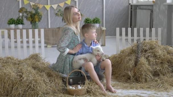Familien besuchen Gemeinschaftsbauernhof, Frau mit Sohn streichelt süße Ziege