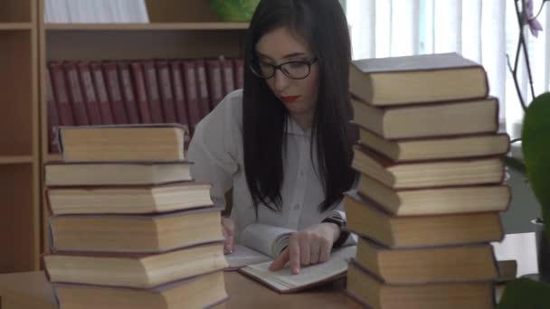Krásná žena s brýlemi v knihovně