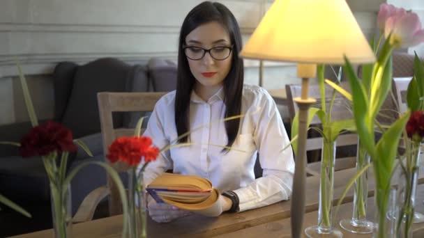 4k bájos lány ül Cafe Reading könyv