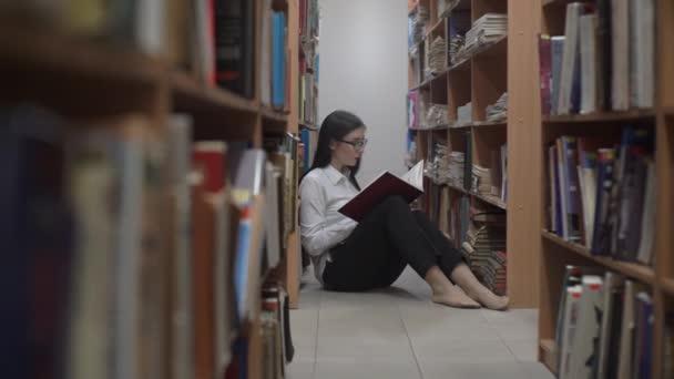 4k lány ül a padlón, és olvassa a könyv a könyvtárban