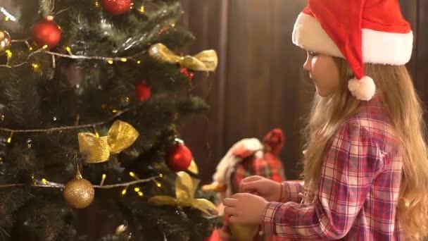 kleines Mädchen schmückt den Weihnachtsbaum