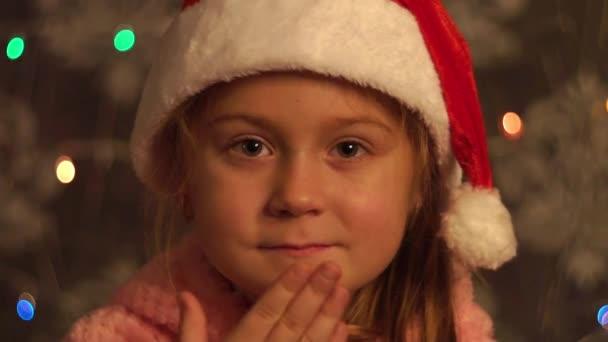 Baby Mädchen senden Luftkuss in Erwartung des Weihnachtsmannes und ein Geschenk zu Weihnachten. neu