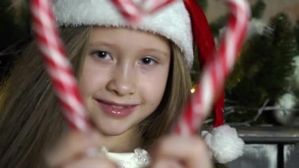 kleines Mädchen hält Zuckerstangen zusammen, um ein Herz zu machen.