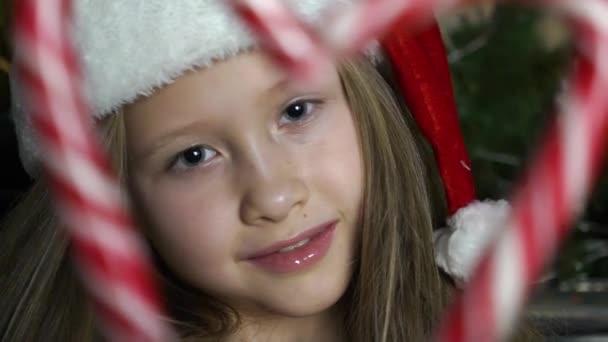 Kaukasisches Mädchen blickt mit Zuckerstangen durch Herzform.