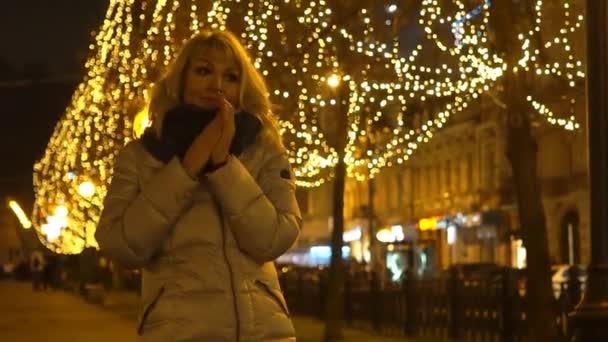 Žena v kabátě procházet osvětlená ulička večer. Zimní krajina.