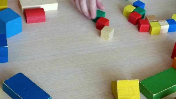 Caucasian kid playing with wooden bricks. Children constructing heart symbol with colored elements. Bright toy love sign. Closeup view.