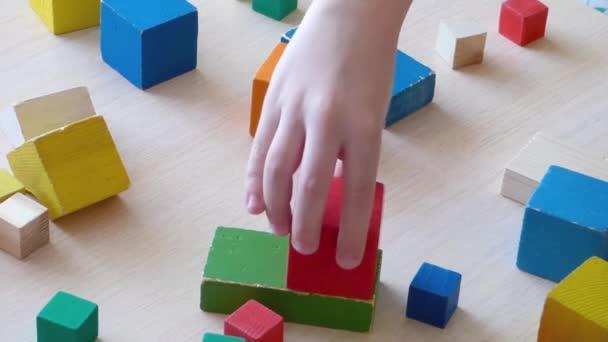 Children and parent playing together with wooden bricks. Children constructing house from colored elements. Bright toy building - real estate theme. Closeup view.
