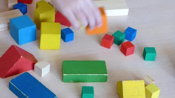 Two Caucasian kids playing together with wooden bricks. Children constructing house from colored elements. Bright toy building - real estate theme. Closeup view.